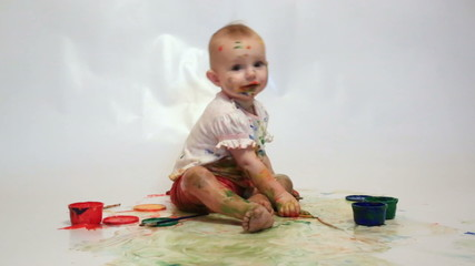 little girl soiled by multi-colored paints sees