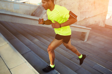 Dark-skinned athlete running up a flight of stairs with speed