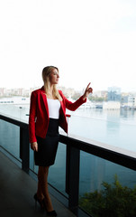 Elegant successful woman standing on balcony of office building
