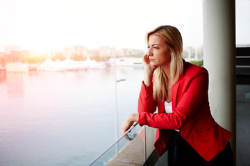 Unhappy successful woman sadly looking out of office balcony