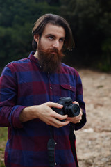 Young bearded man taking photo with his digital camera outdoors