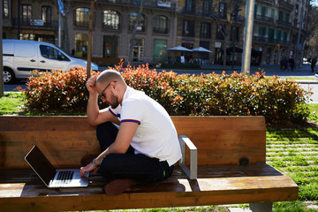 Young modern businessman freelancer working on computer outdoors