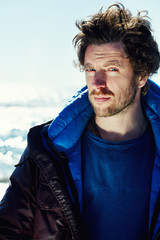 Traveler man in winter jacket on north arctic sea at sunny day