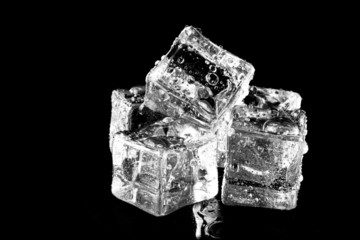 Wet ice cubes on black background. Selective focus