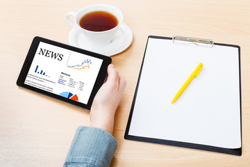 tablet PC with business news on screen at table