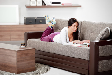 Young Woman Lounging in Living Room on Couch reading book