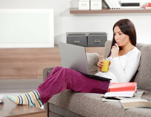 woman in the living room with lap top drinking orange juce