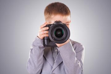 kid holding a dslr camera on a blue background