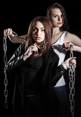 Beautiful young woman smothers the other one with chains