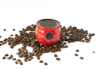 Roasted coffee beans and a cup of coffee on a white background