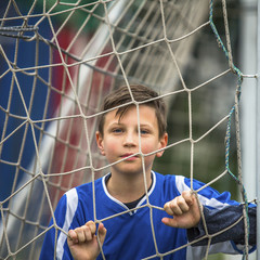 Little football player behind the football goal.