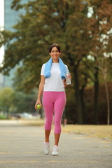 Young woman with towel around neck after fitness exercise
