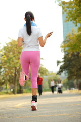 Young beautiful woman training outdoors, running in park