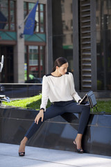 Beautiful business woman sitting on a bench