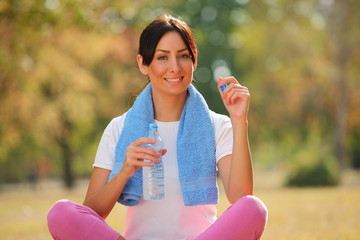 Pretty young woman with bottle of water in hand after fitness