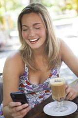 Happy young woman drinking cappuccino sending text message