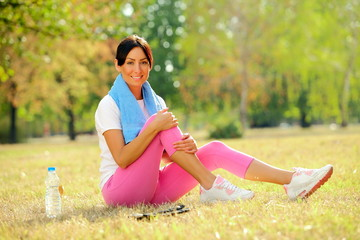 Woman with bottle of water resting after exercising in park.