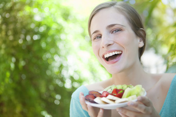 Happy young blonde woman eating fruit salad