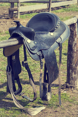 saddle for riding a horse on a wooden fence ranch