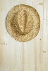 A traditional summer straw hat hanging on a wooden wall