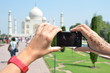 Camera in the hands pointing toTaj Mahal. Agra, India