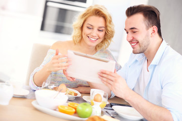 Happy couple eating breakfast and using tablet