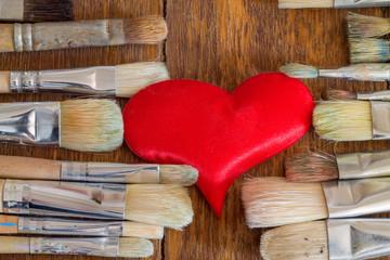 Плюшевое сердце среди художественных кистей