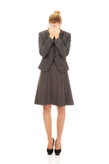 Businesswoman covering face with hands.