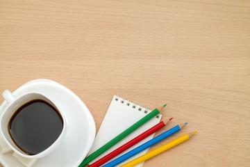 Цветные карандаши, кружка кофе,блокнот, на столе