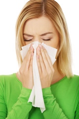 Woman sneezing to tissue.