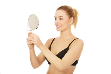 Young woman holding a mirror.