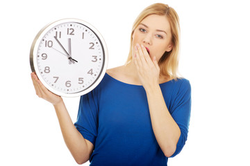 Tired woman holding a clock.