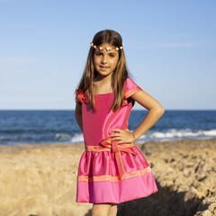 Niña con vestido fucsia y diadema de rosas en el mar
