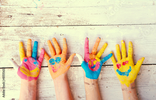Leinwanddruck Bild bunte Kinderhände  mit Gesicht