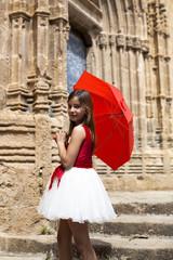 Niña con vestido blanco y rojo y paraguas rojo