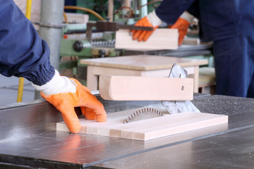 male carpenter using table saw for cutting wood