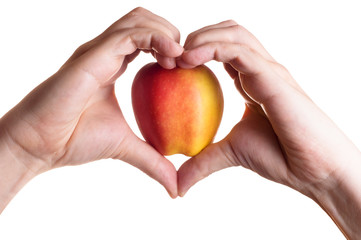 Hands in heart form concluding apple inside isolated
