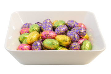 Many chocolate Easter eggs in colorful wrappings in a bowl