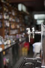 Grifos de cerveza con licores al fondo