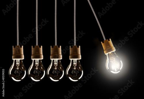 Leinwanddruck Bild Light bulbs in row with single one shinning