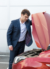 young man in suit looking under the hood of broken car