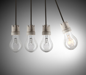 Light bulbs in row with single one shinning