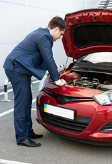man in suit looking under car bonnet
