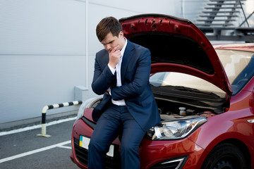 man sitting on bonnet upset because of broken car