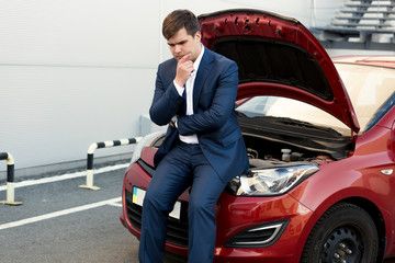 upset businessman sitting on bonnet of broken car