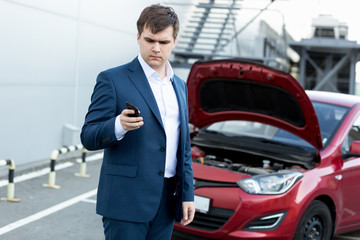 businessman standing at broken car and using telephone