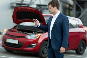 businessman searching in mobile phone how to repair car
