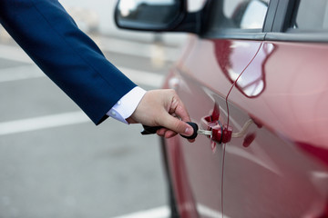 Closeup photo of man in suit opening car door with key