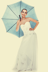 Full length bride in wedding gown holds umbrella