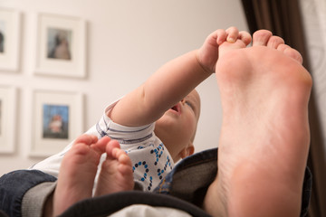 Child playing with the big toe of his father.